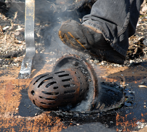 Commercial flat roof drain installation - This is an old cast iron drain and strainer. The strainer's holes and slots are too small, which caused small debris to build up and block water flow.