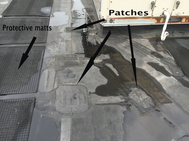 EPDM Roofing Problems - This image shows many repair patches where adhesives have failed due to harmful UV rays.